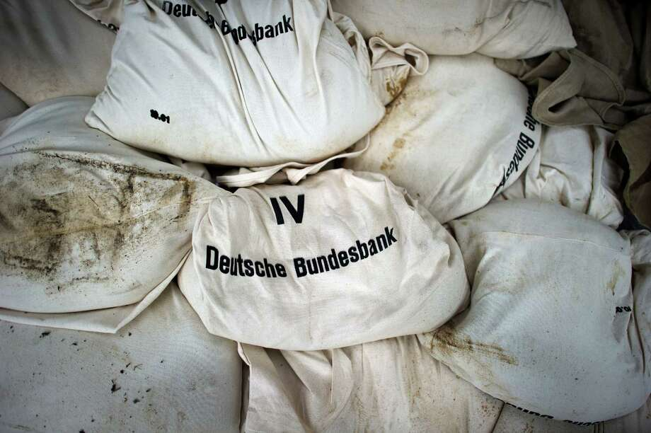 "TOPSHOTS Sandbags with the lettering ""Deutsche Bundesbank"" (German Central Bank) are piled up in protection against the floods in Dresden, eastern Germany, on June 6, 2013. Germany pushed on with frantic efforts to secure soggy river dykes with sandbags, bracing for a surge of the worst floods in over a decade that have claimed 12 lives and forced mass evacuations across central Europe     AFP PHOTO / ARNO BURGI / GERMANY OUTARNO BURGI/AFP/Getty Images Photo: ARNO BURGI, AFP/Getty Images / DPA"