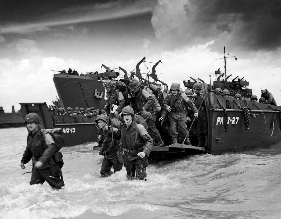 June, 16 1944: US troops disembarking from a landing craft to wade through surf towards beachhead in the days following the invasion of Normandy. Photo: Time Life Pictures, Time & Life Pictures/Getty Image / Time Life Pictures