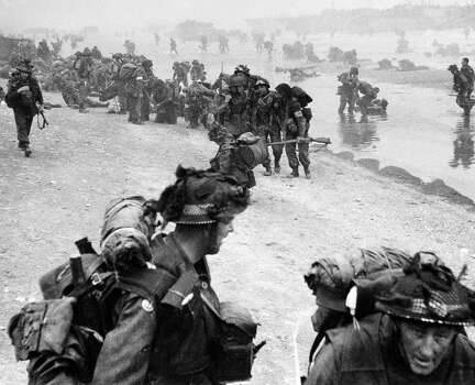D-Day: Troops pour ashore at one of the Normandy beaches during the D Day invasion, Red Cross men attend to casualties. Photo: Popperfoto, Popperfoto/Getty Images / Popperfoto