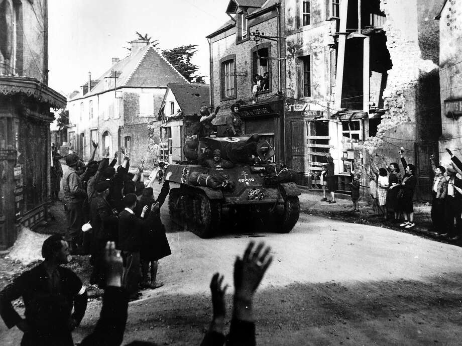 D-Day:A French armored column passing through the small French town of St Mere Eglise on D-Day, gets a warm welcome from the inhabitants. Photo: Popperfoto, Popperfoto/Getty Images / Popperfoto