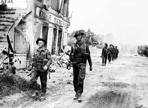 D-Day Plus Two: British soldiers cross  the village of Douet, after the town of Bayeux fell, after Allied forces stormed the Normandy beaches. D-Day is still one of the world's most gut-wrenching and consequential battles, as the Allied landing in Normandy led to the liberation of France which marked the turning point in the Western theater of World War II. Photo: STF, AFP/Getty Images / 2010 AFP