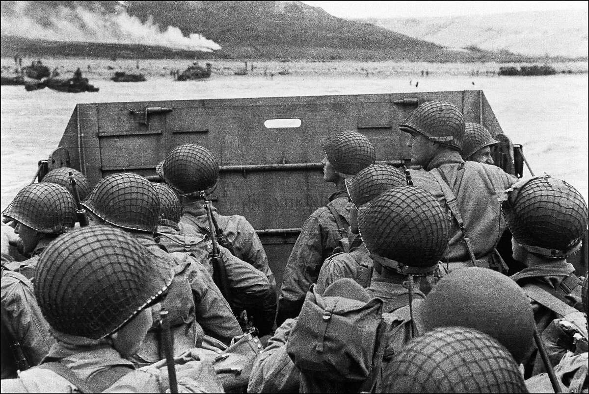 D-Day: American assault troops in a landing craft huddle behind the shield approaching Utah Beach while Allied forces are storming the Normandy beaches on D-Day.