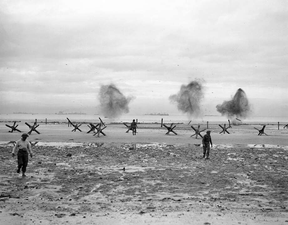 D-Day Plus Three:Royal Navy Commandos of the Landing Craft Obstacle Clearance Units running to get clear while obstacles are blown up at La Riviere. Photo: IWM/Getty Images, IWM Via Getty Images / IWM (A 23993)