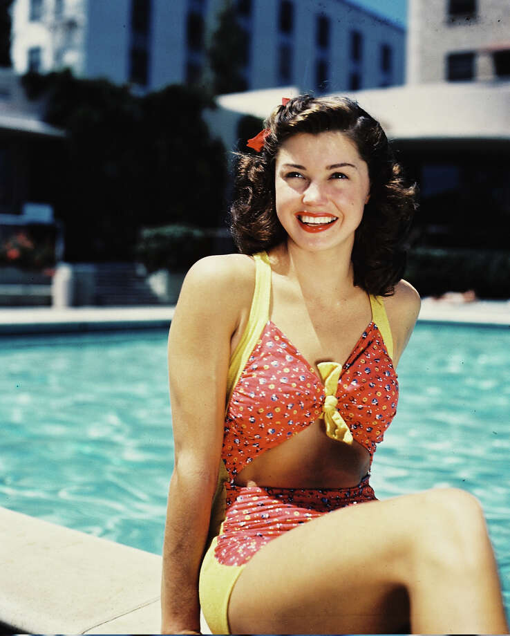 Esther Williams, US actress and former Olympic swimmer, wearing a red-and-yellow bathing costume, smiling as she poses at the edge of a swimming pool, circa 1945. Photo: Silver Screen Collection, Getty Images / 2011 Silver Screen Collection