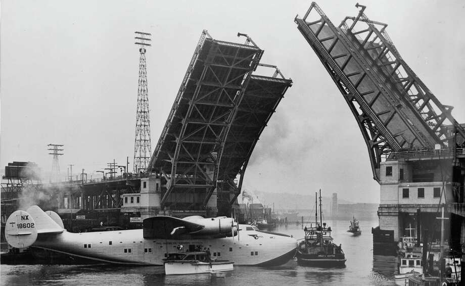 On May 31, 1938, the first Clipper was barged down the Duwamish River from Boeing's plant in preparation for the first flight. This is actually the second Clipper being being edged sideways by two tugboats through the West Spokane Street Bridge. Photo: SEATTLE P-I ARCHIVE 1938