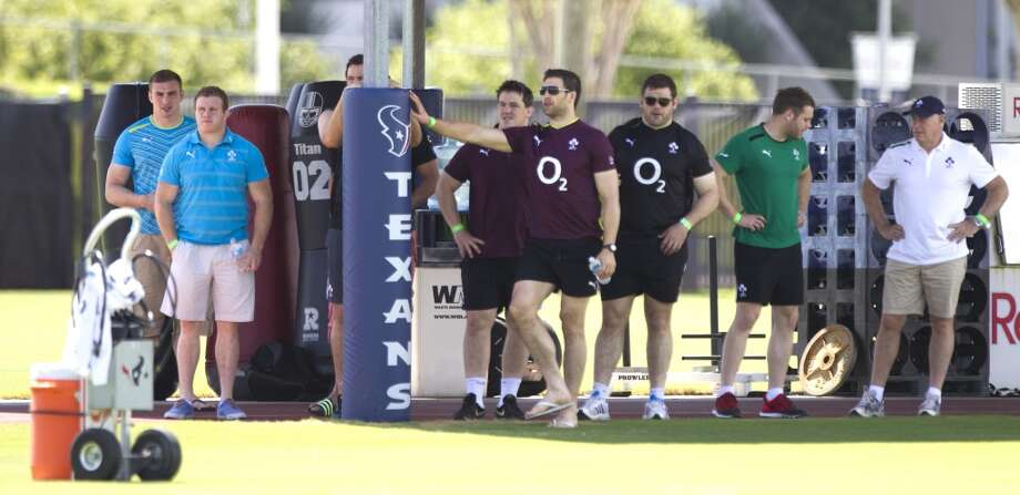 The Irish rugby team stands in the shade while watching the Texans practice during OTAs at the Methodist Training Center. The Irish rugby team in is Houston to play the United States men's national rugby team on Saturday at BBVA Compass Stadium.