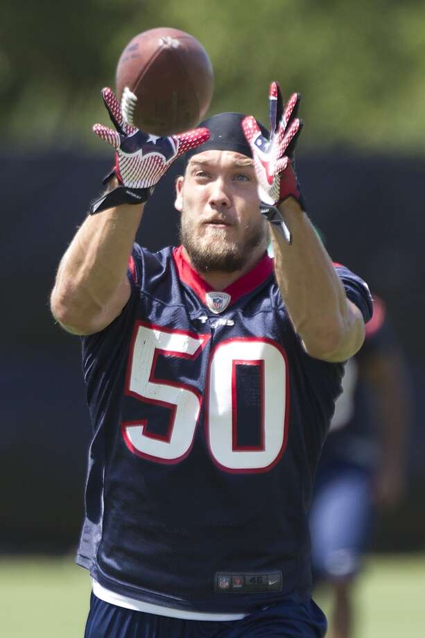 Texans linebacker Brian Braman reaches out to catch a ball while running a drill.