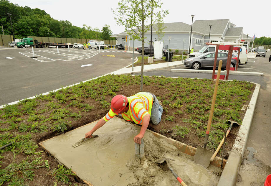 Anthony Oliveira, with John J. Brennan Construction Company based in Shelton, smoothes the drying concrete that will become the base to a power station for plug-in vehicles at the newly opened Darien-North rest area between exits 12 and 13 along Interstate 95 northbound on Thursday, June 6, 2013. The opening comes after more than a year of renovations. Photo: Jason Rearick / Stamford Advocate