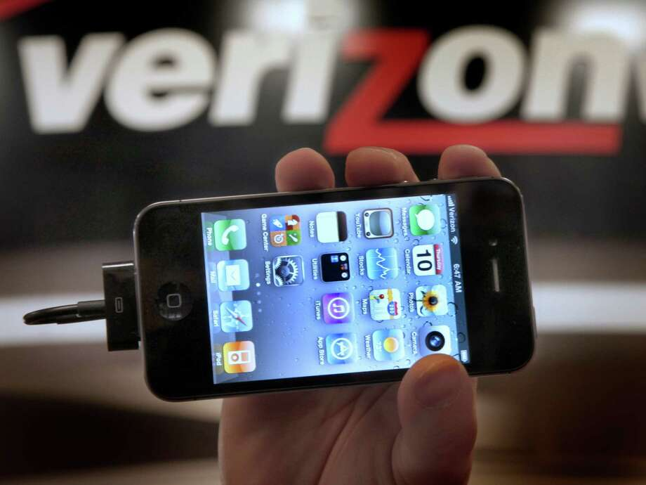 """FILE - In this Feb. 10, 2011 file photo, Chris Cioban, manager of the Verizon store in Beachwood, Ohio, holds up an Apple iPhone 4G. Britain's Guardian newspaper says the National Security Agency is currently collecting the telephone records of millions of U.S. customers of Verizon under a secret court order. The newspaper said Wednesday, June 5, 2013 the order was issued in April and was good until July 19. The newspaper said the order requires Verizon on an """"ongoing, daily basis"""" to give the NSA information on all telephone calls in its systems, both within the U.S. and between the U.S. and other countries. Photo: Amy Sancetta"""