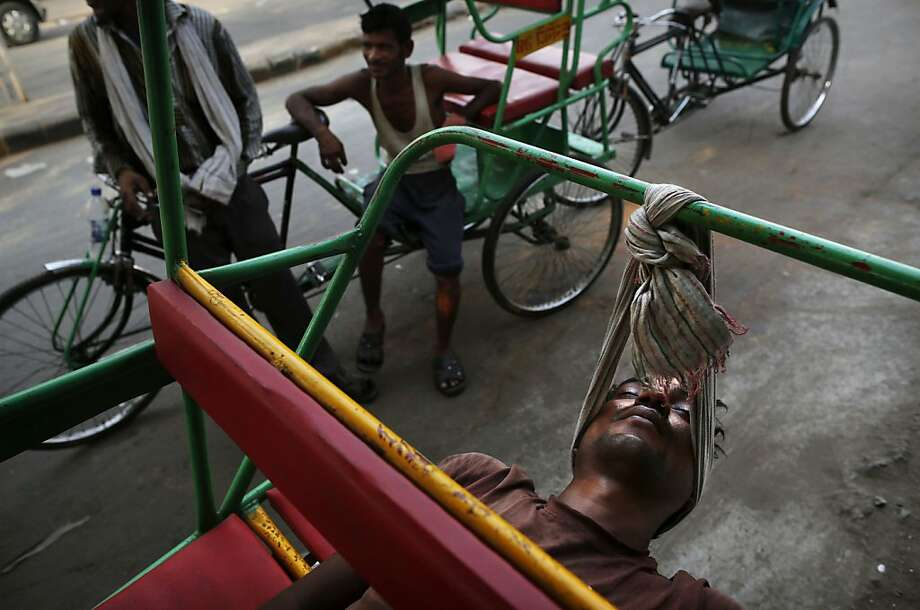 Neck hammock:An Indian tricycle rickshaw walla hangs his head in a scarf in order to catch a few winks in New Delhi. Many rickshaw drivers sleep on their trikes   because they have no permanent residence in the city and also to protect them from   theft. Photo: Kevin Frayer, Associated Press