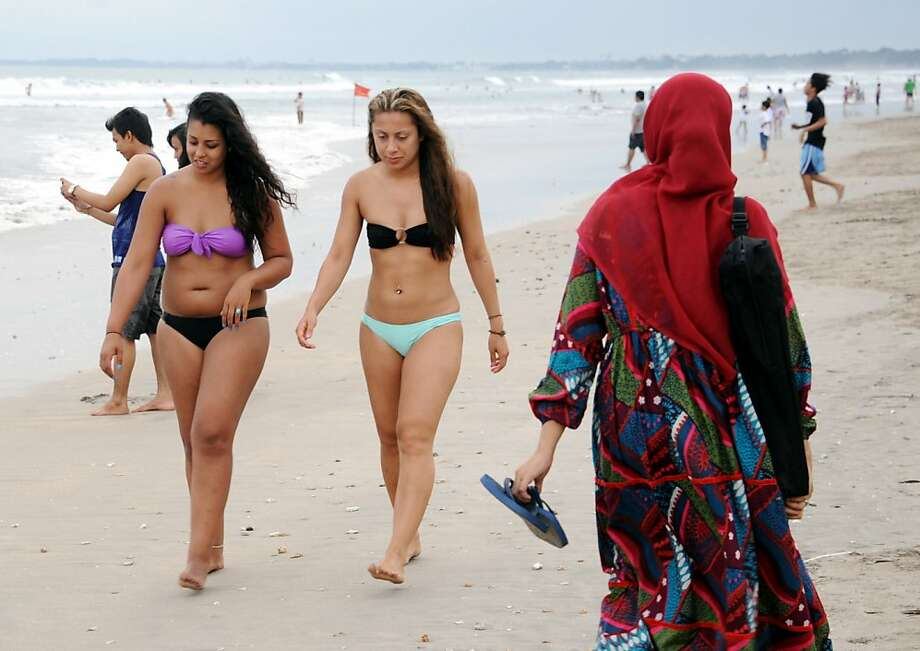 Beauty pageant coverup: A Muslim woman passes bikini-clad tourists at Kuta beach on Indonesia's resort island of Bali. Contestants in this year's Miss World beauty pageant will not wear bikinis in the annual parade in order to avoid offending the nation's Muslim majority. Photo: Sonny Tumbelaka, AFP/Getty Images