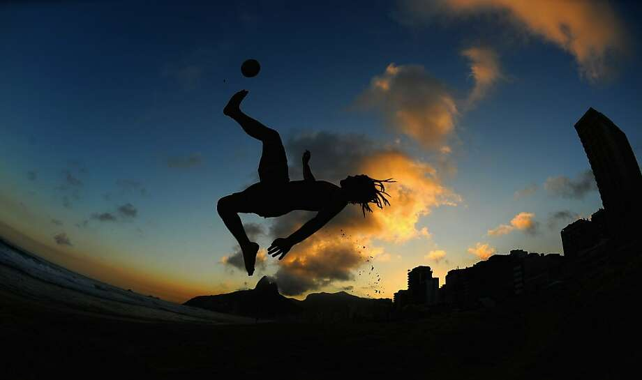 Shooting from the flip: A sand soccer player shows how a scissors kick is done on Ipanema beach ahead of 