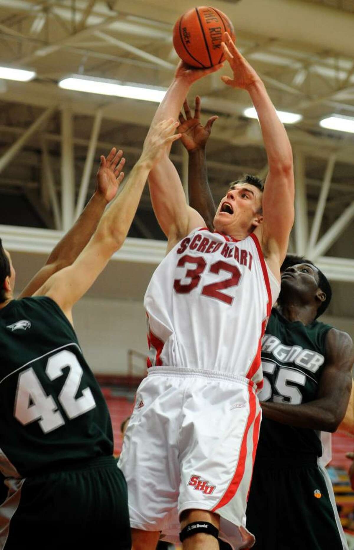 Sacred Heart's Liam Potter attempts a shot as Wagner's Ryan Schrotenboer, left, and Michael Orock guard him during the first half of Thursday night's game at the Pitt Center.