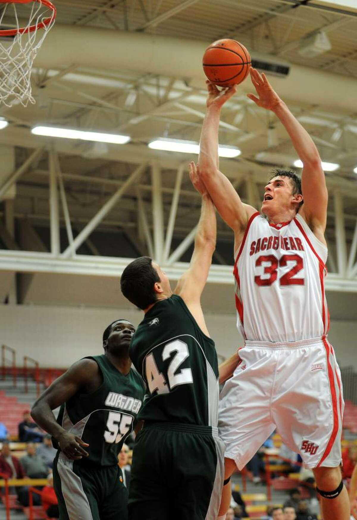 Sacred Heart's Liam Potter puts up the ball as Wagner's Ryan Schrotenboer defends during the first half of Thursday night's game at the Pitt Center.