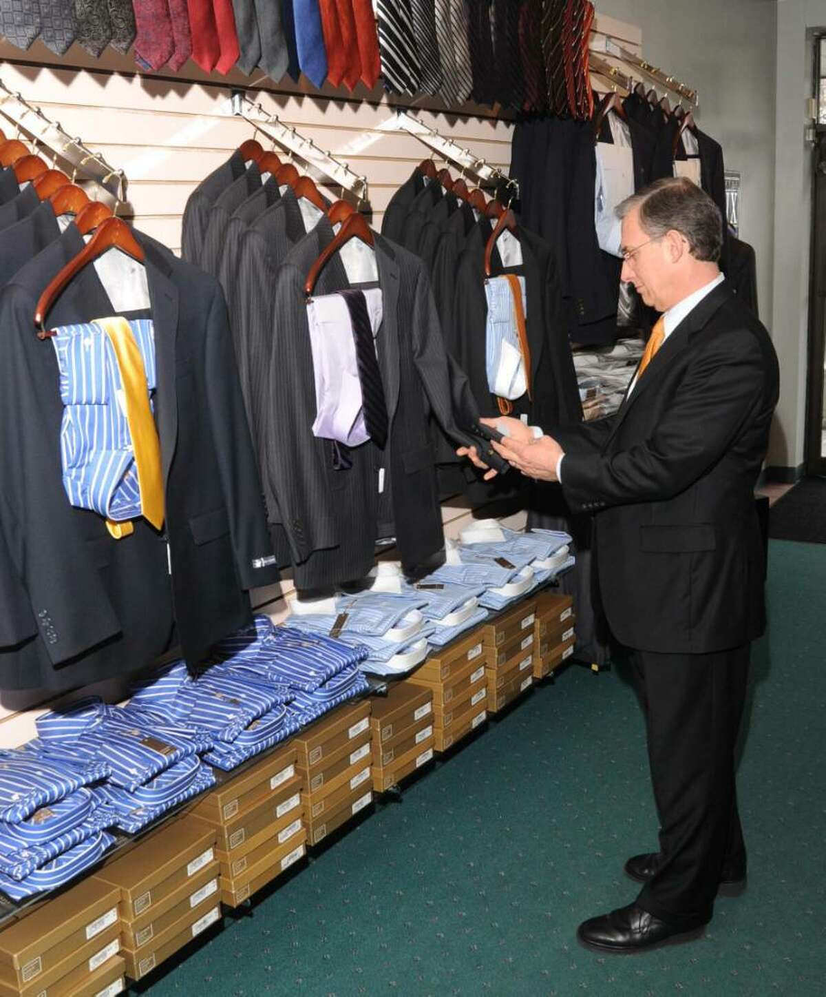 Albert Quell, owner of Bogey's Formal Wear, at 71 Newtown Rd., Danbury, CT, check the lable on a ready- made suit in the showroom, on Friday, Jan. 8, 2010.