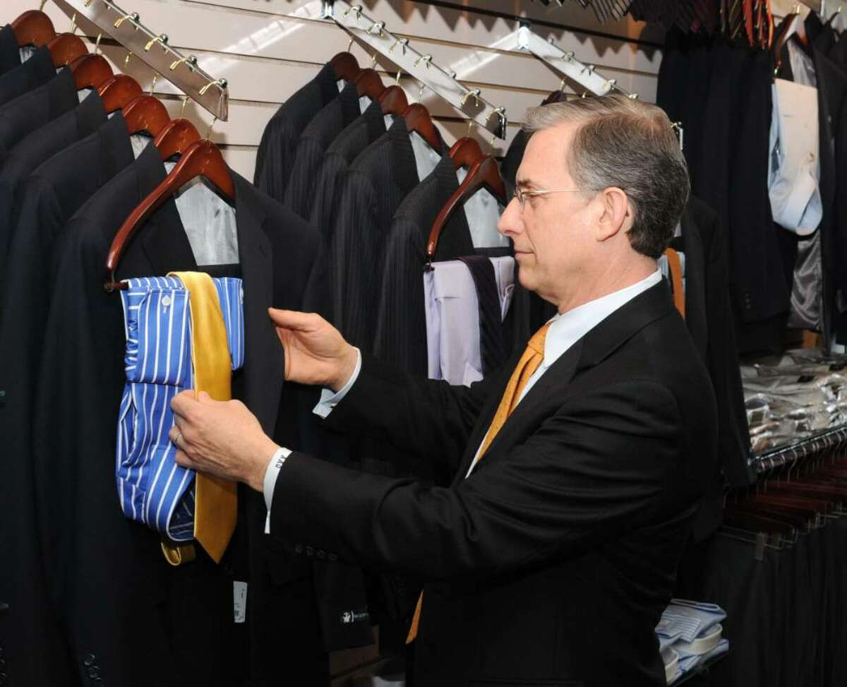 Albert Quell, owner of Bogey's Formal Wear, at 71 Newtown Rd., Danbury, CT, adjust a display of ready- made suits in the showroom, on Friday, Jan. 8, 2010.