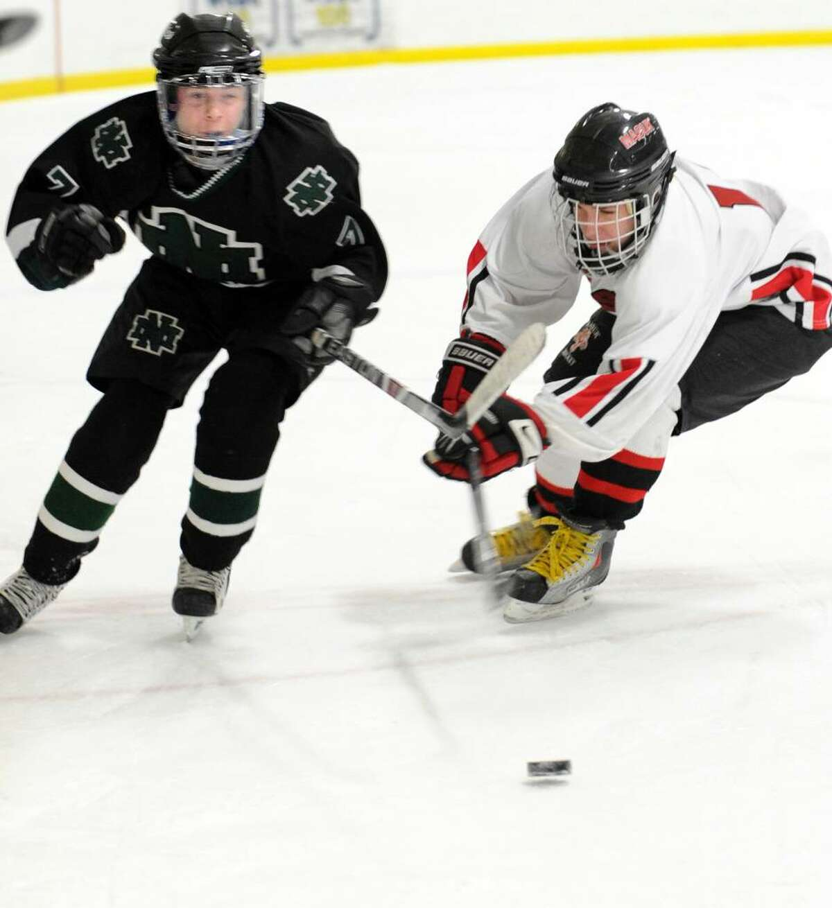 New Milford's Matt Dieter and Masuk's Tyler Dushay mix it up on the ice during the first period of Wednesday night's game at The Rinks at Shelton.