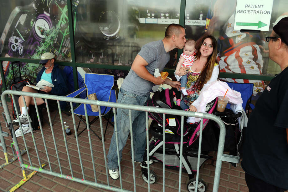 Jeff Gonzales, of Bristol, kisses his daughter Riley Gonzales, 5 months, as mom Taylor Ashker, of Naugatuck, holds her outside the Webster Bank Arena in Bridgeport, Conn. on Thursday June 6, 2013. They just arrived to get a spot to wait in line to get free dental work starting at 6 a.m. on Friday morning which will be given by the Connecticut Mission of Mercy. This is their 6th annual free dental clinic held Friday and Saturday and will help over 2000 people who need everything from extractions to a basic cleaning. Photo: Christian Abraham / Connecticut Post