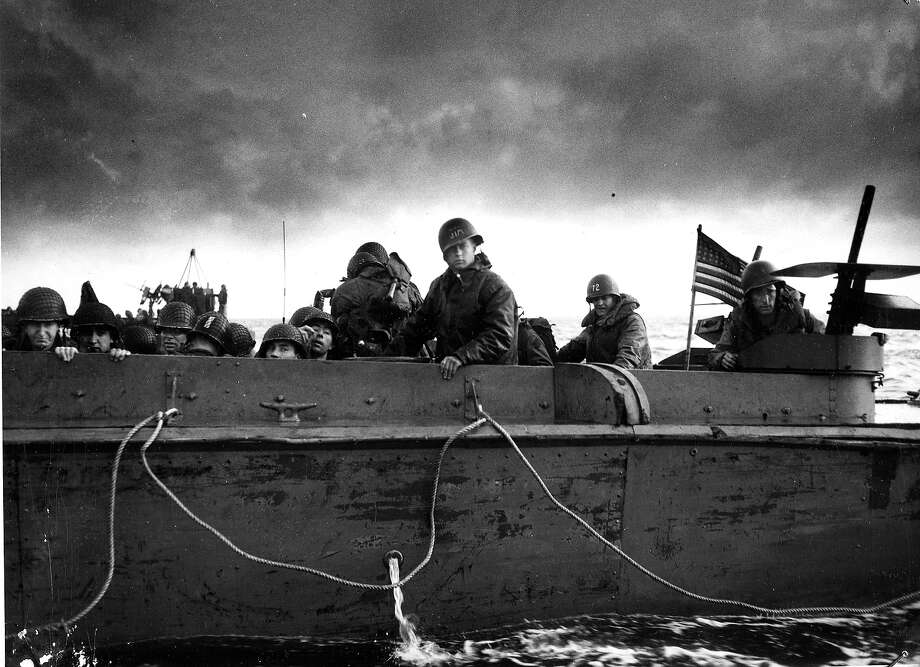 D-Day Plus Two: Grim and determined, these American soldiers head towards the French coast as the American flag flies from the stern of their US Coast Guard landing barge as it speeds toward the invasion shore. Photo: PhotoQuest, Getty Images / Archive Photos