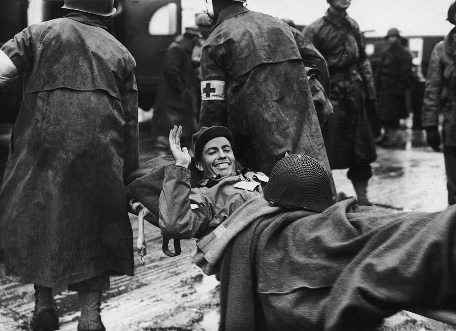 10th June 1944:  A wounded American soldier smiles and waves as he is carried on a stretcher by medics, while being transported to England from France during World War II. The soldier probably took part in the D-Day invasion of Normandy on June 6. Photo: New York Times Co., Getty Images / Archive Photos