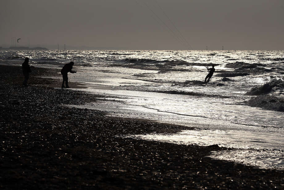 People walk and kitesurf on the beach close to where the allied landings took place in June 1944, on June 5, 2013 near Caen, France. Across Normandy several hundred of the surviving veterans of the Normandy campaign are gathering to commemorate the 69th anniversary of the D-Day landings which eventually led to the Allied liberation of France in 1944. Next year, which will mark the 70th anniversary of the landings, is widely expected to be the last time that the veterans will gather in any great number. Photo: Matt Cardy, Getty Images / 2013 Getty Images