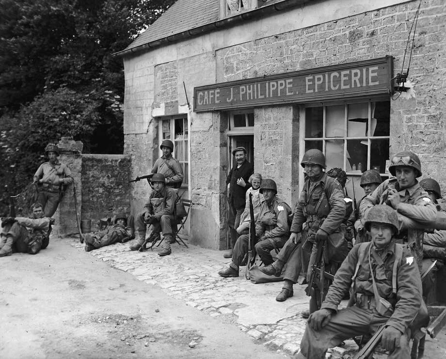 20th June 1944:  American soldiers rest in front of a rural grocery store after advancing inland from their D-Day invasion of Normandy, France,. A French citizen smiles from the doorway. The soldiers wears their helmets and uniforms, holding rifles. Photo: R. Gates, Getty Images / Archive Photos
