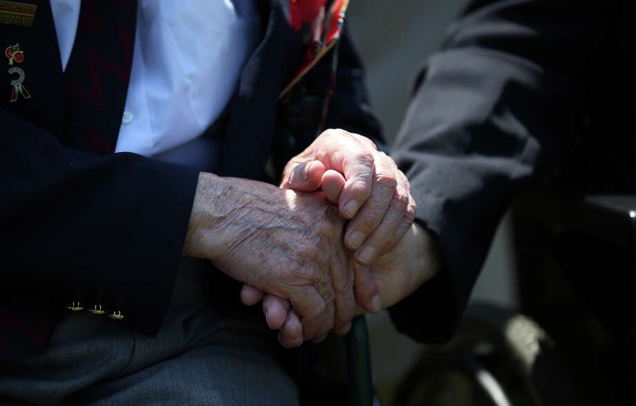 Two Normandy Veterans clasp hands at a remembrance and wreath laying ceremony to commemorate the start of the D-Day landings at Bayeux War Cemetery on June 6, 2013 in Bayeux, France. Across Normandy several hundred of the surviving veterans of the Normandy campaign are gathering to commemorate the 69th anniversary of the D-Day landings which eventually led to the Allied liberation of France in 1944. Next year, which will mark the 70th anniversary of the landings, is widely expected to be the last time that the veterans will gather in any great number. Photo: Matt Cardy, Getty Images / 2013 Getty Images