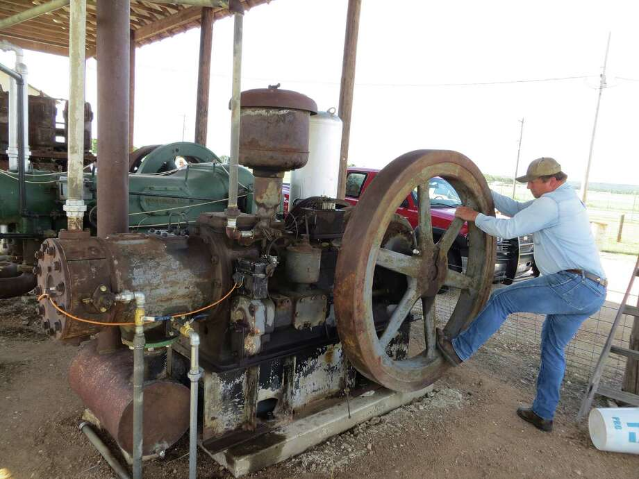 Brian Roeder turns the flywheel on a recently-restored 1930s Superior brand 35 horsepower engine into the proposition for starting it. Members of the Hill Country Antique Tractor & Engine Club spent about a year restoring the engine once used in a petroleum field. A hundred or more engines and at least that  many tractors will be on display on Friday and Saturday at the Gillespie County Fairgrounds in Fredericksburg. Zeke MacCormack Photo: Zeke McCormack, San Antonio Express-News / San Antonio Express-News