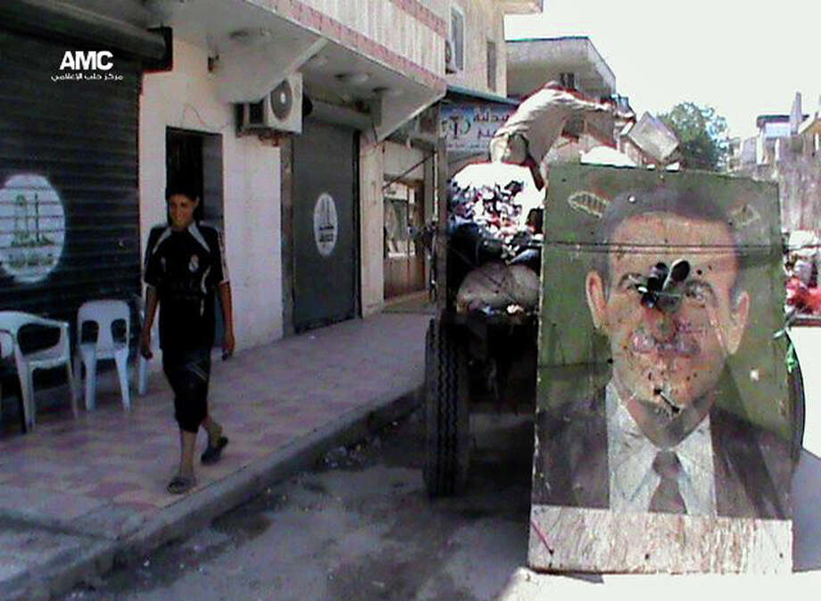 This citizen journalism image provided by Aleppo Media Center AMC which has been authenticated based on its contents and other AP reporting, shows a poster of late Syrian President Hafez Assad on a garbage truck, in Aleppo, Syria, Thursday, June 6, 2013. Syrian troops and their Lebanese Hezbollah allies captured a strategic border town Wednesday after a grueling three-week battle, dealing a severe blow to rebels and opening the door for President Bashar Assad's regime to seize back the country's central heartland. The regime triumph in Qusair, which Assad's forces had bombarded for months without success, demonstrates the potentially game-changing role of Hezbollah in Syria's civil war. (AP Photo/Aleppo Media Center AMC) Photo: Anonymous, HOEP / Aleppo Media Center AMC