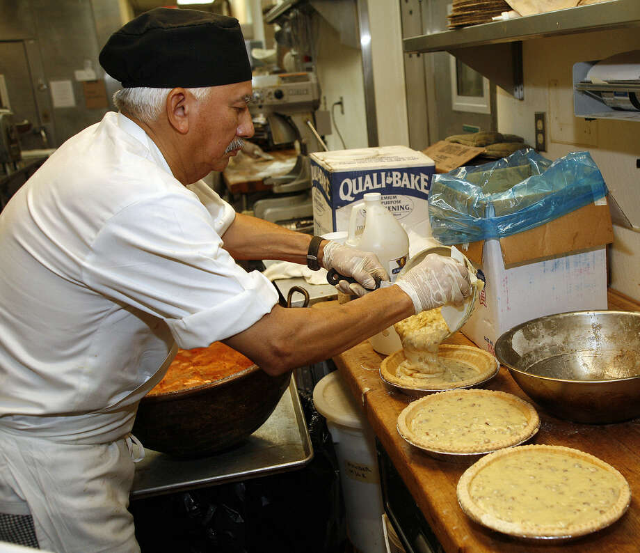 Antonio Sanchez pours maple pecan pie filling into baked pie shells at Earl Abel's. Photo: Express-News File Photo