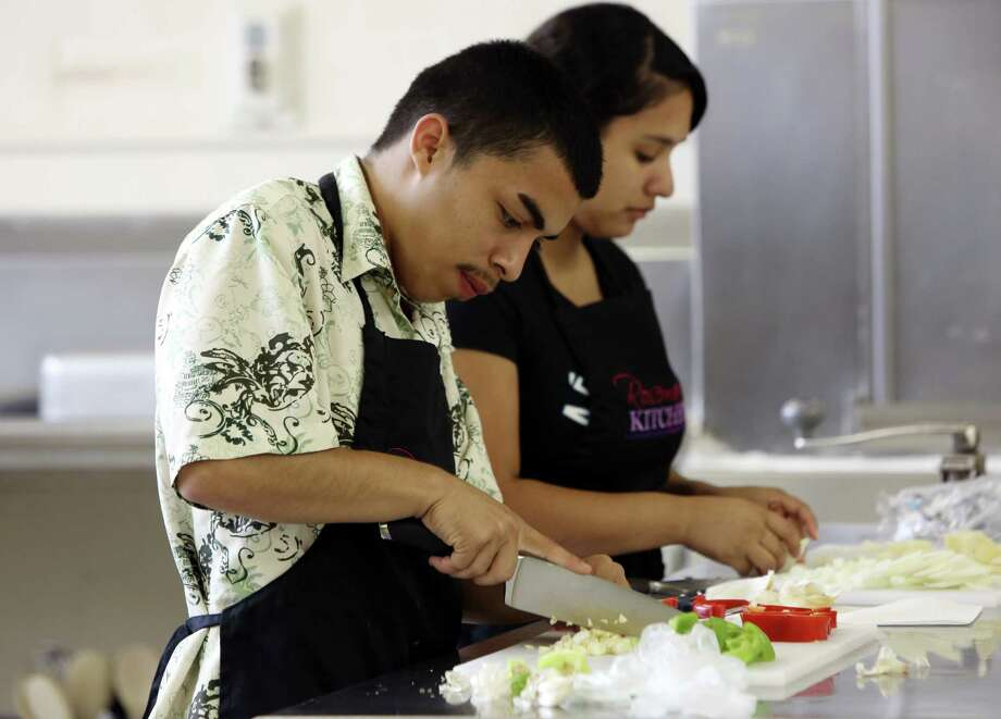 Roger Espinosa and Abigail Cano cut vegetables as part of their training in Rosemary's Kitchen, a culinary arts training program that is part of SA Youth, a dropout recovery program. The culinary program is named after catering legend Rosemary Kowalski.