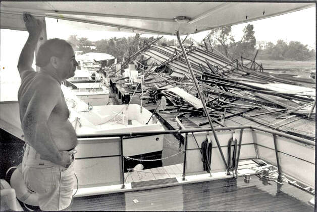 Jim Snell stands on his boat and looks over the damage at the Beaumont Boat Club.  The Storm tore the boat house apart.  File Photo of The Beaumont Enterprise