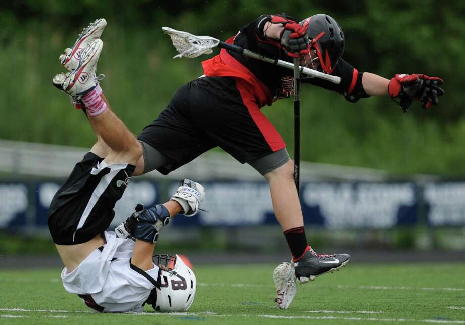 Bethel's Kevin Schlacht, left, gets tangled up with Pomperaug defender Seamus Conway during Bethel's 17-9 win over Pomperaug in the SWC Dvision 2 boys lacrosse championship game at Immaculate High School in Danbury, Conn. on Thursday, June 6, 2013. Photo: Tyler Sizemore / The News-Times