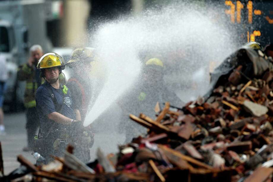 A firefighter sprays the debris in the aftermath of a building collapse, Thursday, June 6, 2013, in Philadelphia. On Wednesday, the building under demolition collapsed onto a neighboring thrift store, killing six people and injuring 14, including one who was pulled from the debris nearly 13 hours later. (AP Photo/Matt Rourke) Photo: Matt Rourke, STF / AP