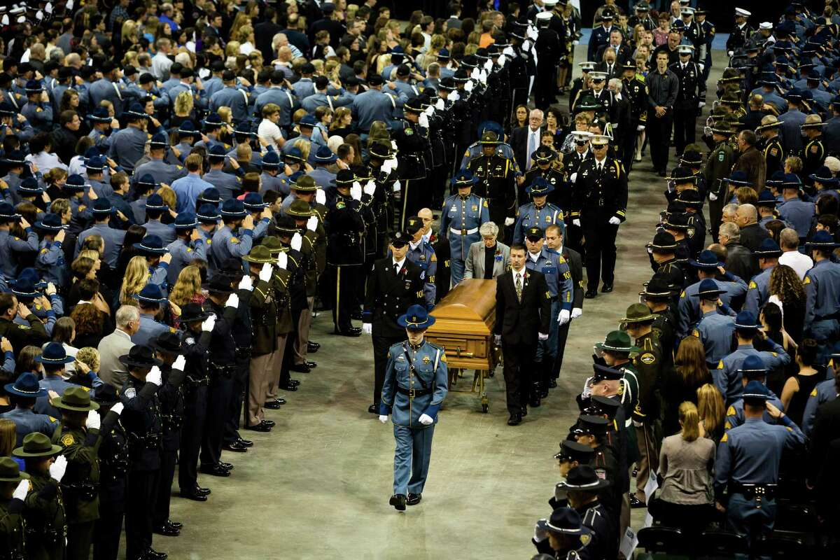 With thousands watching, the casket carrying the body of the late Washington State Patrol Trooper Sean M. O'Connell Jr. is removed following a memorial service Thursday, June 6, 2013, at the Comcast Arena in Everett. Following a 13-mile vehicular procession, friends, family and law enforcement attended the ceremony. O'Connell was killed in a collision with a truck while working Conway.