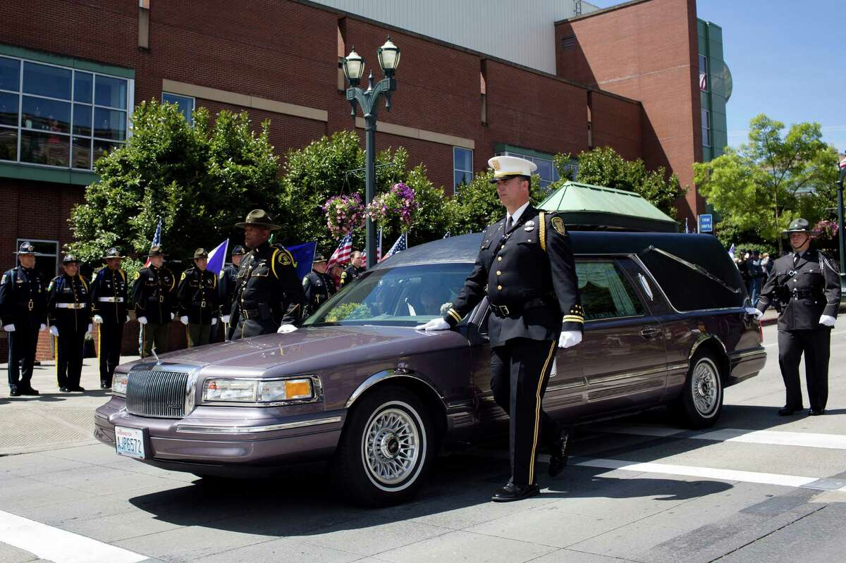 The hearse carrying the casket of the late Washington State Patrol Trooper Sean M. O'Connell Jr. arrives at the Comcast Arena Thursday, June 6, 2013, in Everett. Following a 13-mile vehicular procession, thousands of friends, family and law enforcement attended the ceremony. O'Connell was killed in a collision with a truck while working Conway.