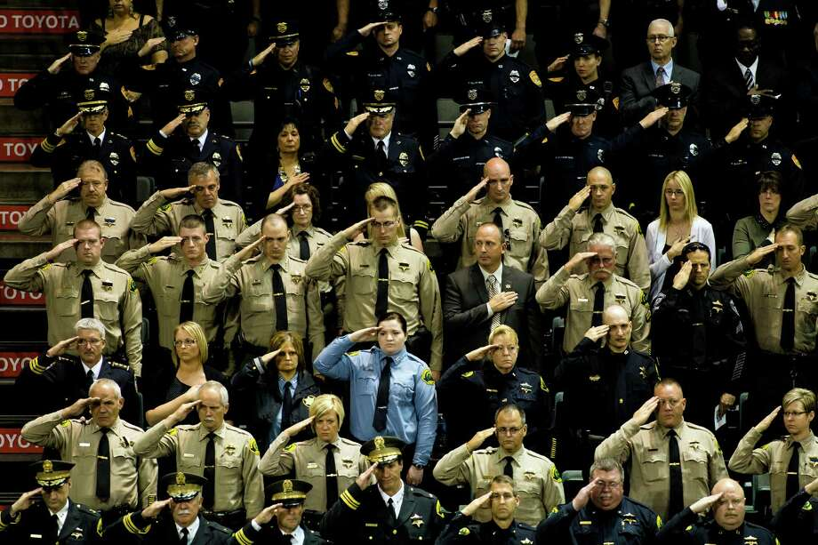 Law enforcement officials salute during a memorial service for the late Washington State Patrol Trooper Sean M. O'Connell Jr. Thursday, June 6, 2013, at the Comcast Arena in Everett. Following a 13-mile vehicular procession, thousands of friends, family and law enforcement attended the ceremony. O'Connell was killed in a collision with a truck while working Conway. Photo: JORDAN STEAD, SEATTLEPI.COM / SEATTLEPI.COM