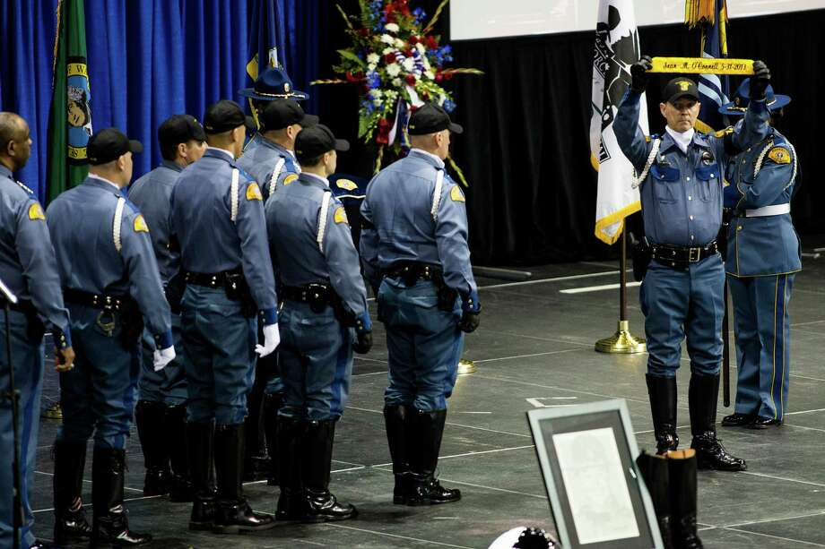 Washington State Patrol troopers hold up a banner with the name of the late Sean M. O'Connell Jr. at a memorial service Thursday, June 6, 2013, at the Comcast Arena in Everett. Following a 13-mile vehicular procession, thousands of friends, family and law enforcement attended the ceremony. O'Connell was killed in a collision with a truck while working Conway. Photo: JORDAN STEAD, SEATTLEPI.COM / SEATTLEPI.COM