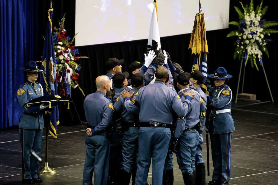 Washington State Patrol troopers tie a banner with the name of the late Sean M. O'Connell Jr. to a flag at a memorial service Thursday, June 6, 2013, at the Comcast Arena in Everett. Following a 13-mile vehicular procession, thousands of friends, family and law enforcement attended the ceremony. O'Connell was killed in a collision with a truck while working Conway. Photo: JORDAN STEAD, SEATTLEPI.COM / SEATTLEPI.COM