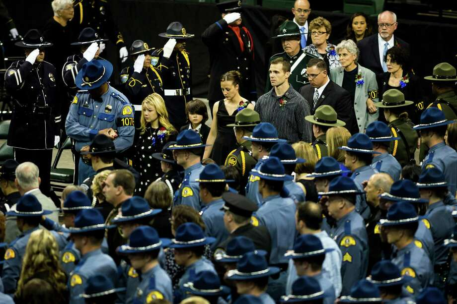 Alissa O'Connell, center left, widow of Washington State Trooper Sean O'Connell, is escorted to her seat at the beginning of a memorial service for her husband Thursday, June 6, 2013, at the Comcast Arena in Everett. Following a 13-mile vehicular procession, thousands of friends, family and law enforcement attended the ceremony. O'Connell was killed in a collision with a truck while working Conway. Photo: JORDAN STEAD, SEATTLEPI.COM / SEATTLEPI.COM