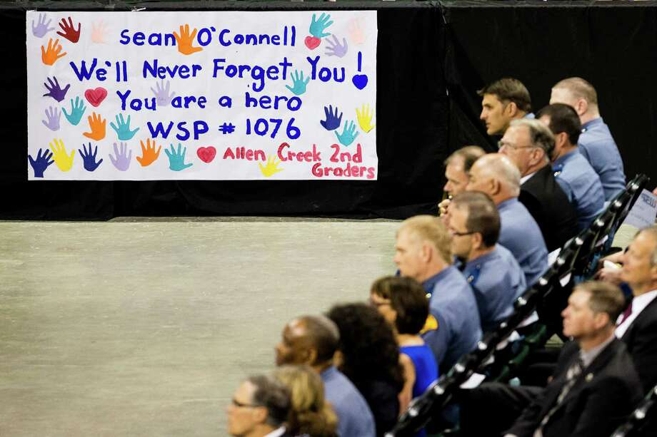 A sign made by second graders stands out during a memorial service for the late Washington State Patrol Trooper Sean M. O'Connell Jr. Thursday, June 6, 2013, at the Comcast Arena in Everett. Following a 13-mile vehicular procession, thousands of friends, family and law enforcement attended the ceremony. O'Connell was killed in a collision with a truck while working Conway. Photo: JORDAN STEAD, SEATTLEPI.COM / SEATTLEPI.COM