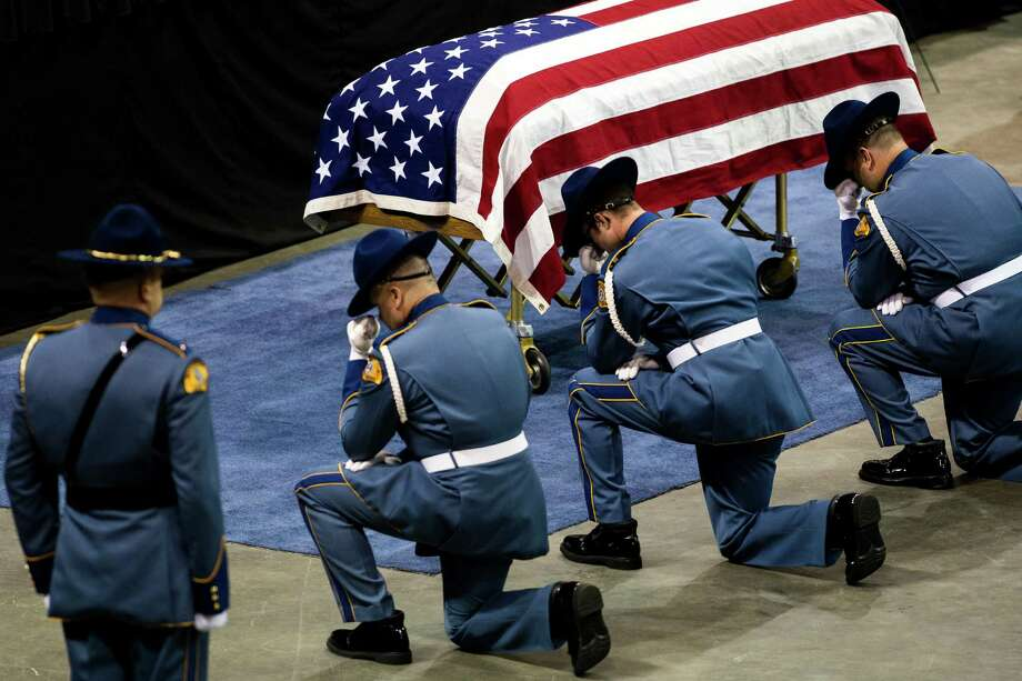 Washington State Patrol troopers kneel before a casket during a memorial service for the late Washington State Patrol Trooper Sean M. O'Connell Jr. Thursday, June 6, 2013, at the Comcast Arena in Everett. Following a 13-mile vehicular procession, thousands of friends, family and law enforcement attended the ceremony. O'Connell was killed in a collision with a truck while working Conway. Photo: JORDAN STEAD, SEATTLEPI.COM / SEATTLEPI.COM