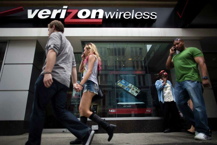"""Pedestrians pass a Verizon Wireless store on Canal Street, Thursday, June 6, 2013, in New York. The Obama administration on Thursday, June 6, 2013, defended the government's need to collect telephone records of American citizens, calling such information """"a critical tool in protecting the nation from terrorist threats."""" Britain's Guardian newspaper reported that the NSA has been collecting the telephone records of millions of Verizon customers under a top secret court order. (AP Photo/John Minchillo) Photo: John Minchillo, FRE / FR170537 AP"""