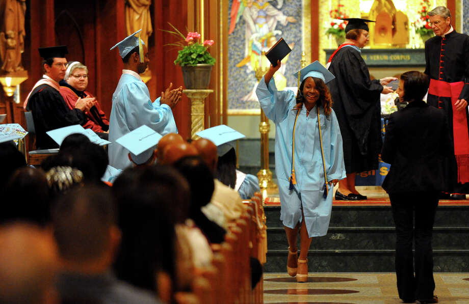 Graduate Marly Verdier waves with her diploma during Kolbe Cathedral Commencement Exercises at St. Augustine Cathedral in Bridgeport, Conn. on Thursday June 6, 2013. Photo: Christian Abraham / Connecticut Post