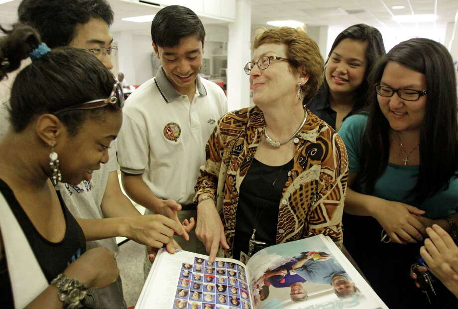 Dr. Kathryn Brown pages through a yearbook Thursday at Bellaire High with seniors Chinyere Stallworth, left front, Alex Mo, Aaron Mao, Bella Yap and Janet Yim, right, on the last day of class. Brown is retiring after 31 years teaching music in HISD. Photo: Melissa Phillip, Staff / © 2013  Houston Chronicle