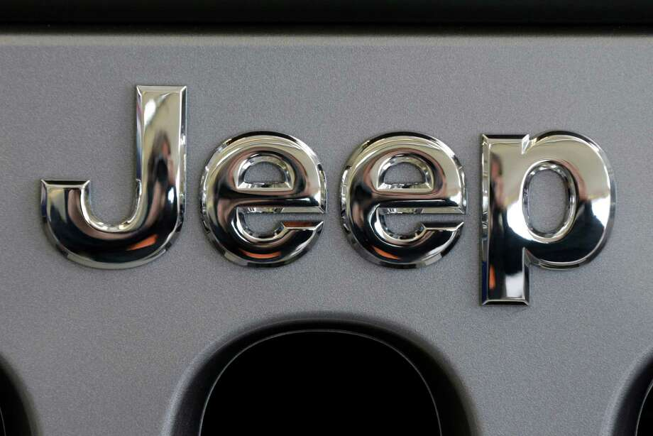 This Feb. 14, 2013 photo shows a Jeep logo on the grill of a Jeep Wrangler at the 2013 Pittsburgh Auto Show in Pittsburgh. Just two days after refusing a government request to recall 2.7 million older-model Jeeps, Chrysler has decided to do two other recalls totaling 630,000 vehicles worldwide, according to documents posted Thursday, June 6, 2013, on the National Highway Traffic Safety Administration website. The automaker will recall more than 409,000 Jeep Patriot and Compass small SUVs across the globe from the 2010 and 2012 model years to fix air bag and seat-belt problems. It's also recalling 221,000 Jeep Wranglers worldwide from 2012 and 2013 to fix transmission fluid leaks. (AP Photo/Gene J. Puskar) Photo: Gene J. Puskar, STF / AP