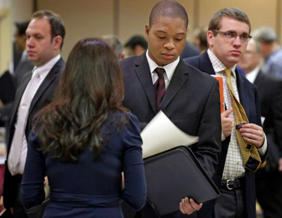 In this May 29, 2013 photo, job seekers wait to speak with Patrice Tosi, of BluePay, second from left, during a career fair in Rolling Meadows, Ill. The number of Americans seeking unemployment benefits fell 11,000 the last week of May 2013 to a seasonally adjusted 346,000, a level consistent with steady job growth. (AP Photo/M. Spencer Green) Photo: M. Spencer Green, STF / AP