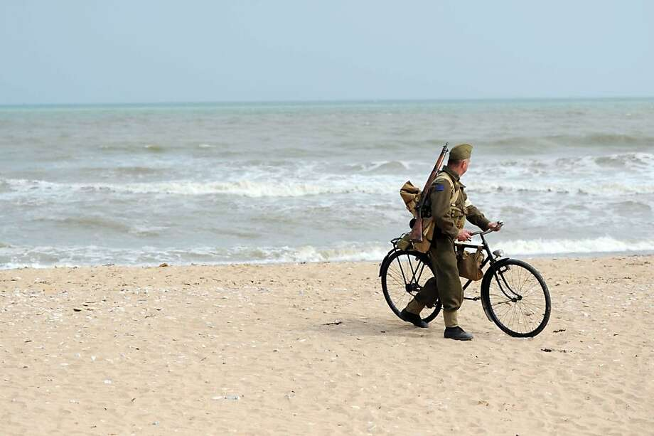 A man dressed as a World War II soldier walks with a bicycle along Juno Beach in Courseulles-sur-Mer, on June 6, 2013, during the commemoration of the 69th anniversary of the D-Day landing in Normandy. As part of D-Day commemorations, a ceremony was held in Courseulles-sur-Mer to mark the 10 year anniversary of the June Beach centre in Courseulles-sur-Mer, Canada's Second World War museum in Normandy. On June 6 1944, American, British, and Canadian troops launched an assault on Nazi German forces which were occupying the northern French coast, in a battle which marked the beginning of the liberation of France and the victory of allied forces over Nazi Germany in the Second World War.  AFP PHOTO / THOMAS BREGARDISTHOMAS BREGARDIS/AFP/Getty Images Photo: Thomas Bregardis, AFP/Getty Images