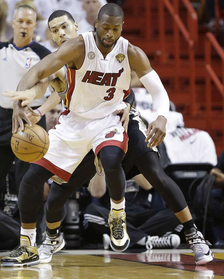 Heat guard Dwyane Wade jockeys for position against Danny Green of the Spurs. Photo: Lynne Sladky, Associated Press