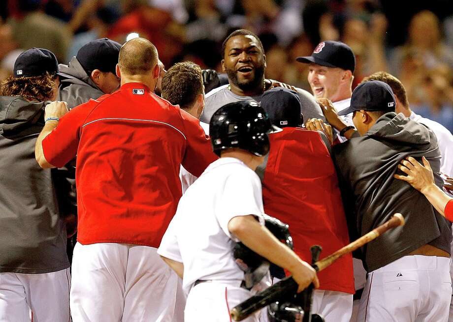 Red Sox designated hitter David Ortiz trotted home to find a mob of teammates celebrating his 11th career walkoff home run. Photo: Jim Rogash, Stringer / 2013 Getty Images